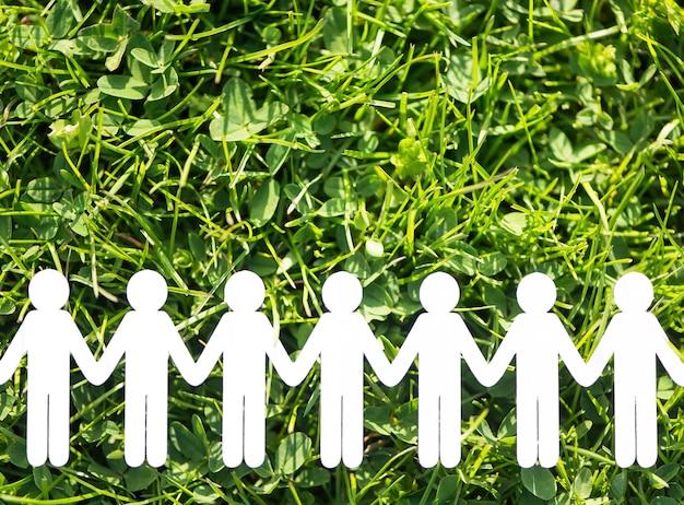 Papierowi ludzie na zielonej trawy tle