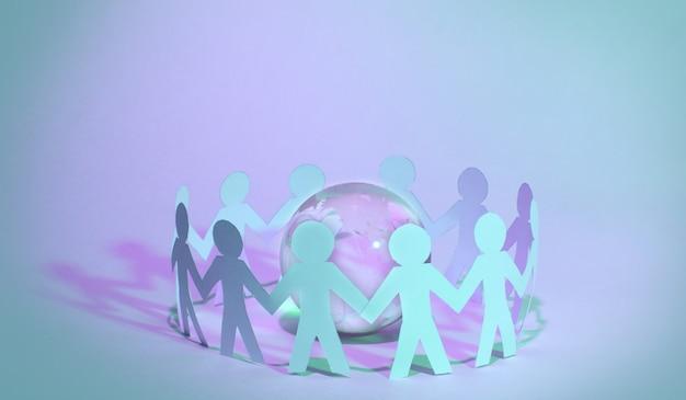Papierowi ludzie stojący w kręgu wokół szklanej kuli
