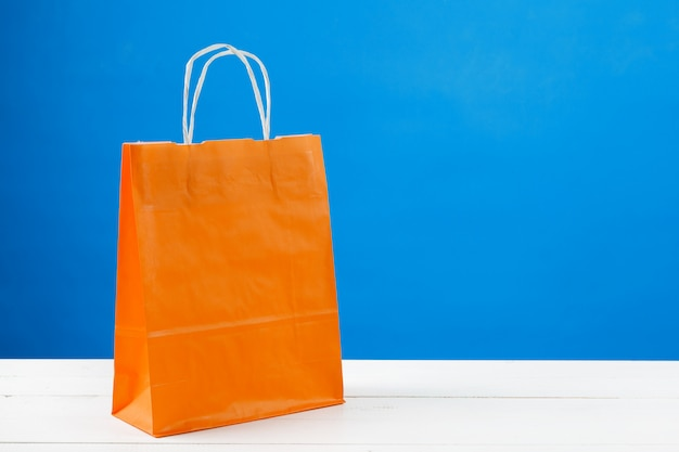 Papierowi torba na zakupy z kopii przestrzenią na błękitnym tle
