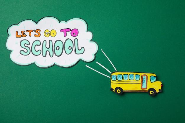 Papierowy autobus szkolny i tekst chodźmy do szkoły na zielono