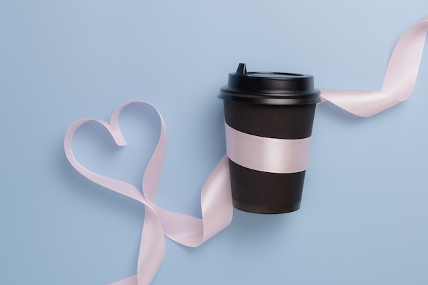 Papierowy czarny kubek do kawy i różowa wstążka w kształcie serca na niebieskim tle. koncepcja walentynki.