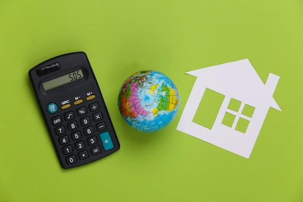 Papierowy dom z kulą ziemską i kalkulatorem na zielono. koncepcja ekologiczna.