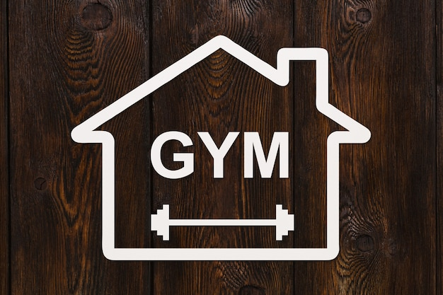Papierowy dom z tekstem siłownia wewnątrz na podłoże drewniane. obraz koncepcyjne sportu streszczenie