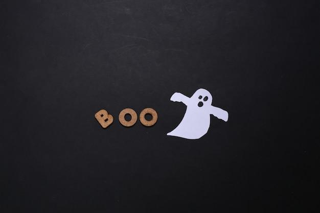 Papierowy duch i słowo boo na czarnym tle. motyw halloween