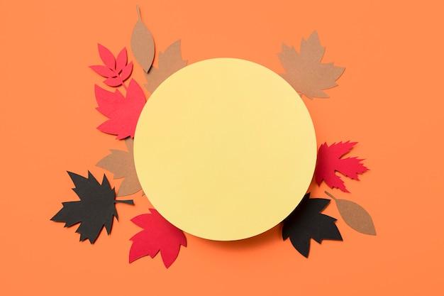 Papierowy jesień liści przygotowania na pomarańczowym tle