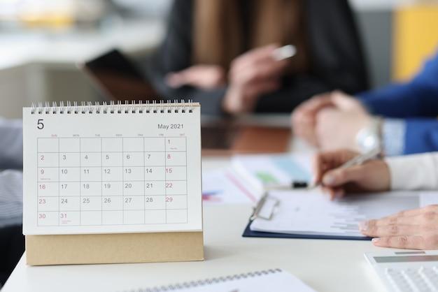 Papierowy kalendarz z luźnymi liśćmi stojący na stole z bliska ludzi biznesu