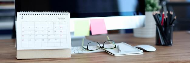 Papierowy kalendarz z luźnymi liśćmi stojący w pobliżu komputera na pulpicie zbliżenie wygodne miejsce pracy