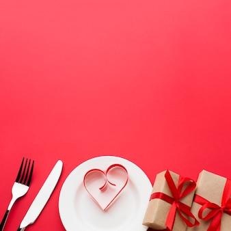 Papierowy kształt serca na talerzu z prezentami i sztućcami