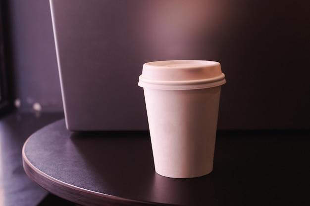 Papierowy kubek do kawy przed laptopem.