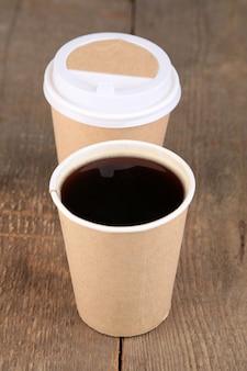 Papierowy kubek kawy na drewnianym stole