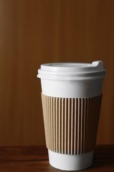 Papierowy kubek kawy na stole, na podłoże drewniane