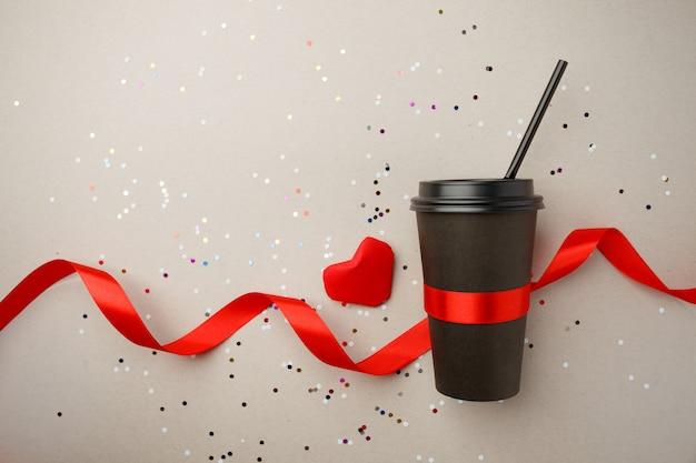 Papierowy kubek kawy ozdobiony czerwonym sercem origami, jedwabną wstążką i konfetti