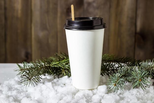 Papierowy kubek kawy w śniegu z gałęziami jodły.