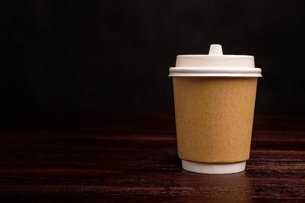 Papierowy kubek na kawę na ciemnym tle