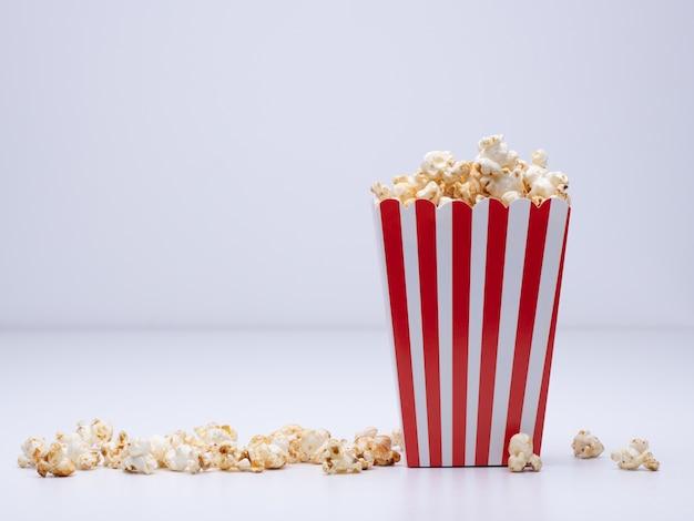 Papierowy kubek popcornu i trochę popcornu rozrzuconego na białej powierzchni