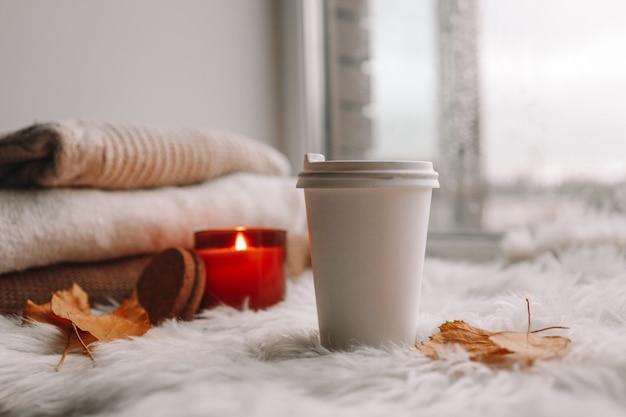 Papierowy kubek z herbatą na parapecie. jesienny nastrój.