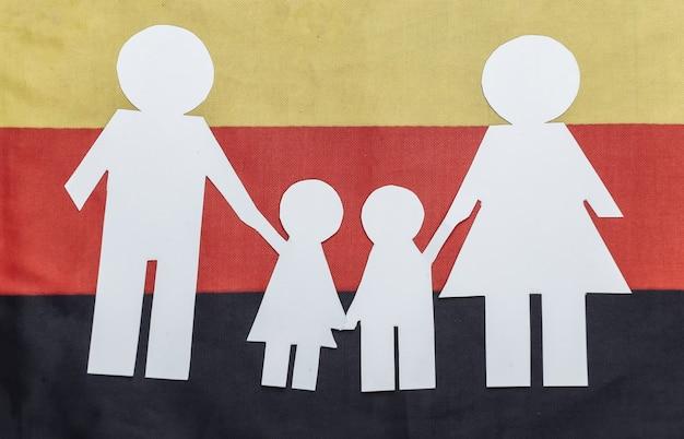 Papierowy łańcuch rodzinny na fladze niemiec. motyw patriotyzmu