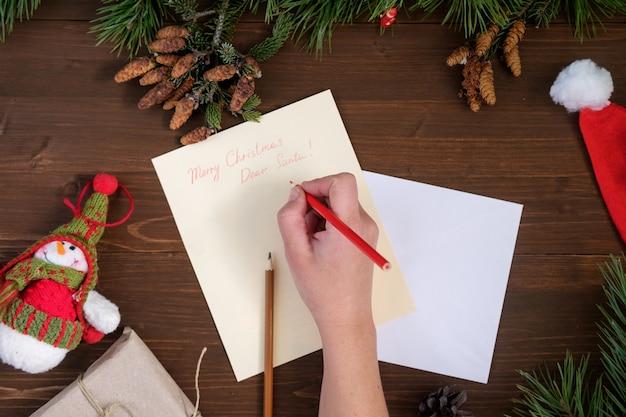 Papierowy list do świętego mikołaja na drewnianym stole z zabawkami, gałązkami sosny, ołówkami i szyszkami jodłowymi
