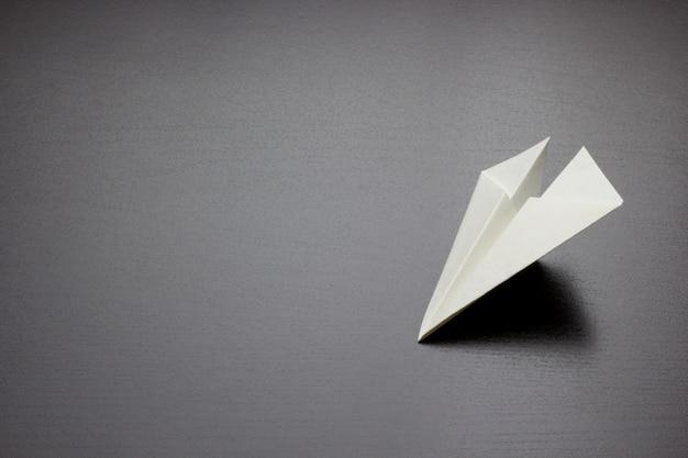 Papierowy lotniczy samolot na ciemnym tle dla projekta