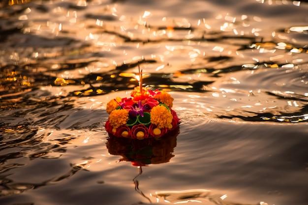 Papierowy lotosowy kwiat z świeczką unosi się na rzece przy nocą w loy krathong festiwalu