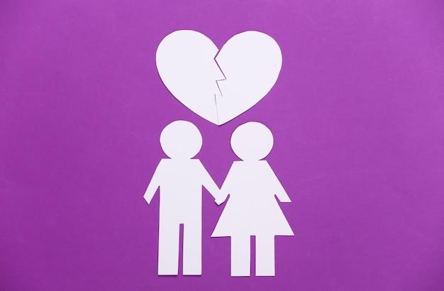 Papierowy mężczyzna i kobieta z czerwonym złamanym sercem na fioletowym.