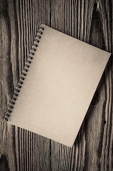 Papierowy notatnik na spirali na białym tle na drewnianych powierzchniach
