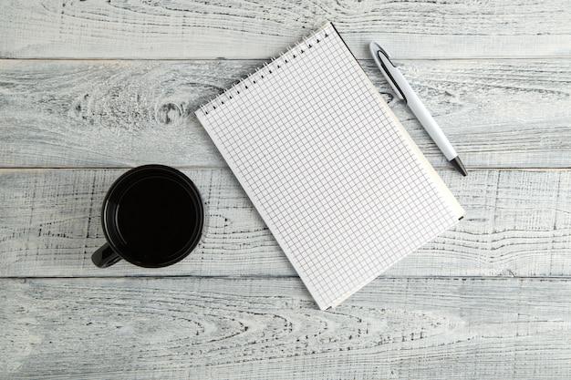 Papierowy notatnik, pióro i filiżanka herbata lub kawa na rocznika podławym białym drewnie, odgórny widok