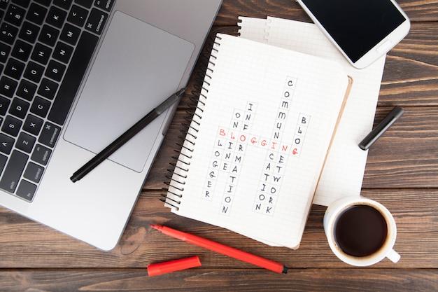 Papierowy notatnik z blogging słowem, laptop computer.social medialny pojęcie