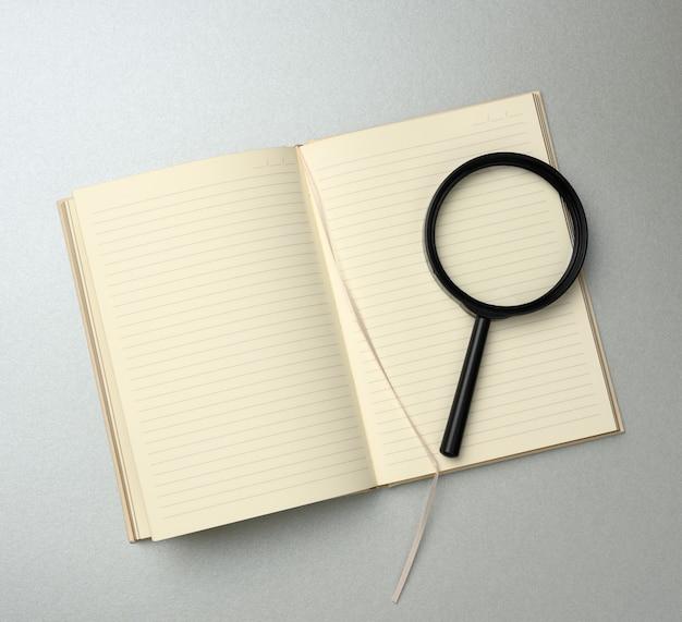 Papierowy notatnik z pustymi białymi kartkami i czarną lupą na szarej powierzchni. powierzchnia na napisy, poszukiwanie rozwiązań i odpowiedzi