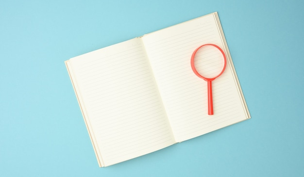 Papierowy notatnik z pustymi białymi kartkami i czerwoną lupą na niebieskim tle. tło do napisów, poszukiwanie rozwiązań i odpowiedzi