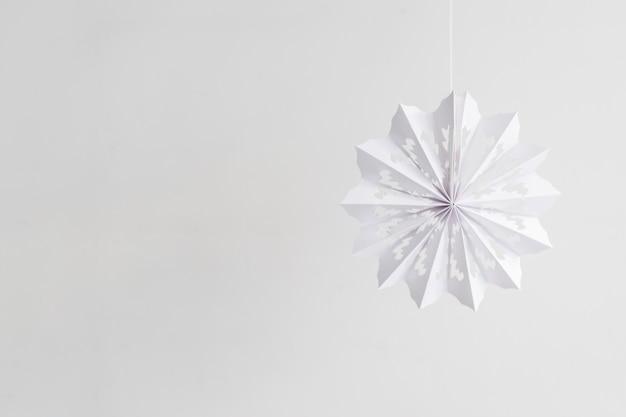 Papierowy płatek śniegu wiszący na arkanie