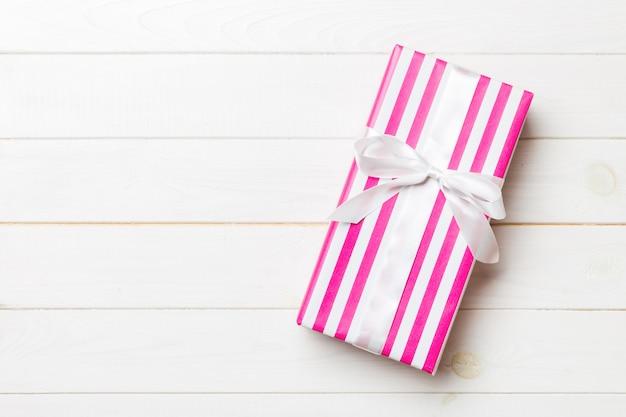 Papierowy prezenta pudełko z coled faborkiem na białym drewnianym tle. widok z góry z miejsca kopiowania koncepcja świąt bożego narodzenia