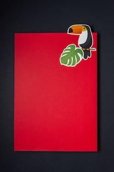 Papierowy ptak i gałąź palmy na pustej czerwonej kartce lub notatce. minimalna koncepcja.