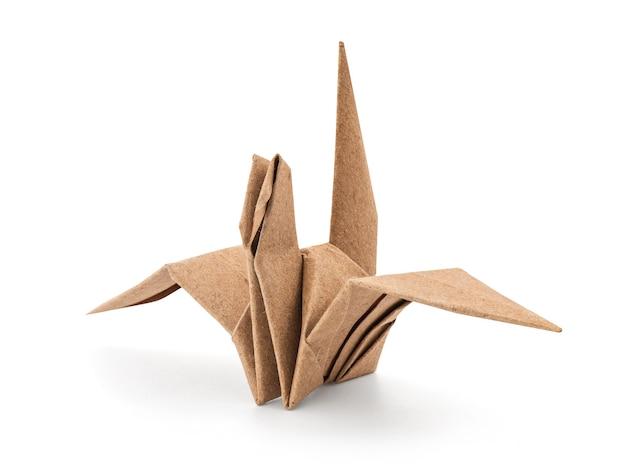 Papierowy ptak złożony ze starego papieru na białym tle na białej powierzchni ze ścieżką przycinającą.