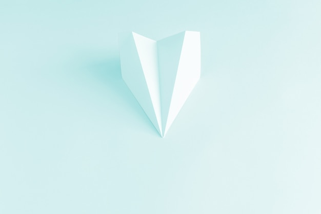 Papierowy samolot na bladoniebieskim tle. modna koncepcja kolorystyczna 2019
