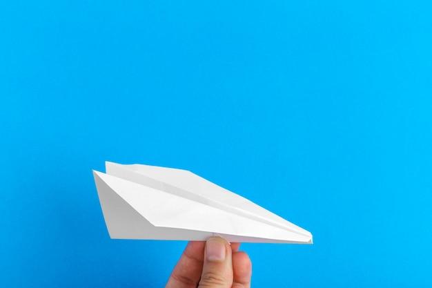 Papierowy samolot na jaskrawym tle trzyma w ludzkiej ręce. koncepcja podróży i turystyki