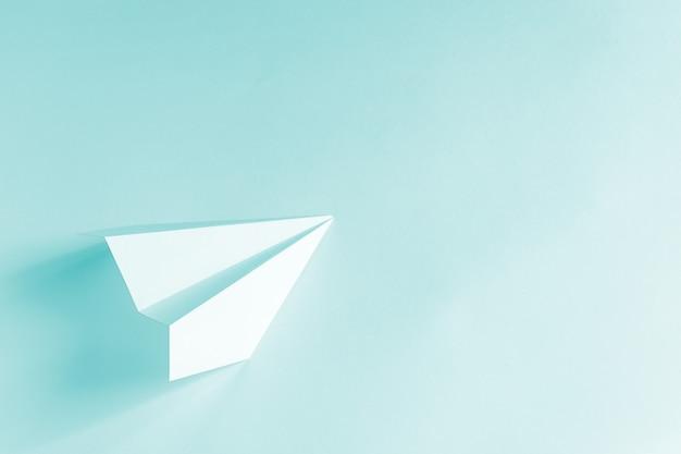Papierowy samolot na jasnoniebieskim tle. modna kolorowa koncepcja