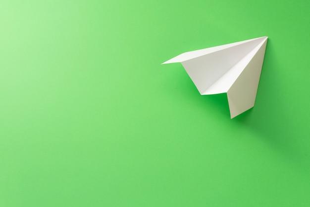 Papierowy samolot na zielonym tle