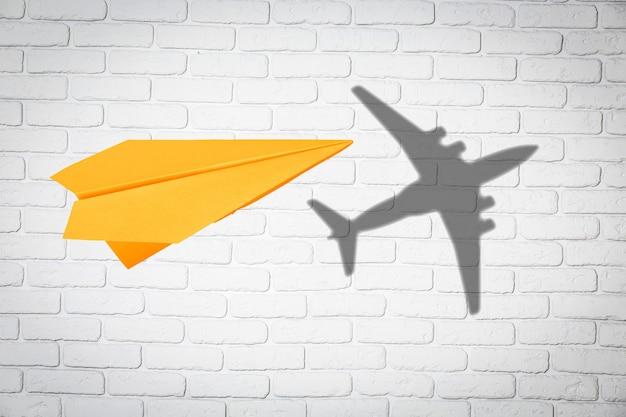 Papierowy samolot w locie z cieniem klasycznego prawdziwego samolotu