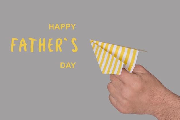 Papierowy samolot w ręku dorosłego mężczyzny z gratulacyjnym napisem happy fathers day
