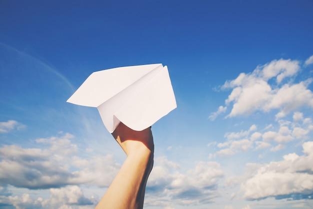 Papierowy samolot w ręku gotowy do lotu