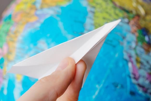 Papierowy samolot w ręku z bliska na kuli ziemskiej