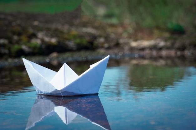 Papierowy statek na wodzie. papierowa łódź origami żeglarstwo.