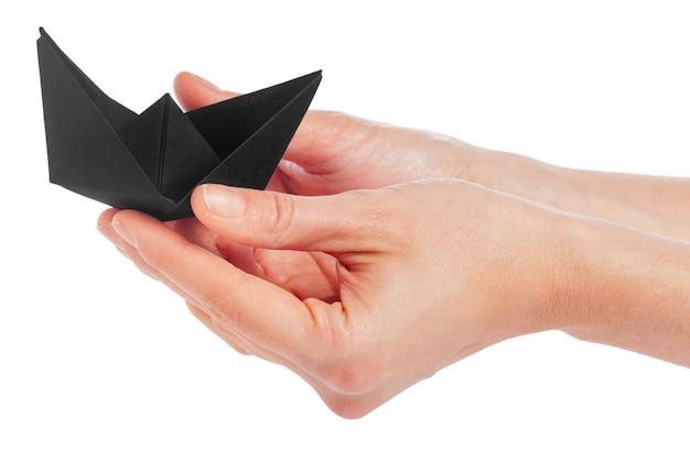 Papierowy statek w żeńskiej ręce