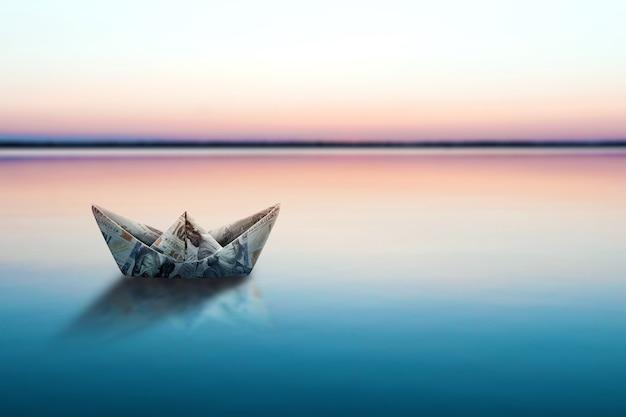 Papierowy statek zrobiony z banknotów, zrobiony z dolarów, unosi się na wodzie na tle pięknego zachodu słońca. origami z pieniędzy, finansowy model biznesowy, kopia przestrzeń.