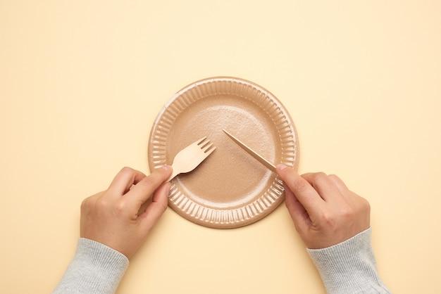 Papierowy talerz i kobiece dłonie trzymają jednorazowy widelec i nóż