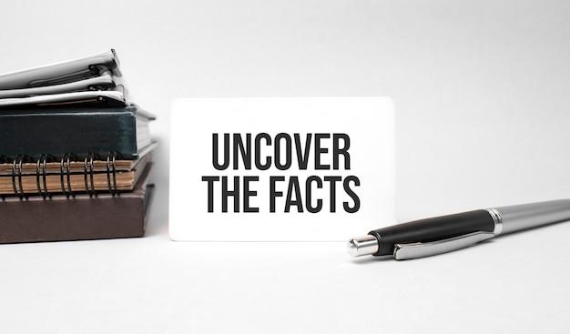 Papierowy talerz, okulary, notatnik w stosie, długopis i tekst odkryj fakty na wizytówce