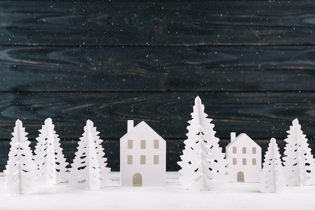 Papierowy zimy miasto na drewnianym tle