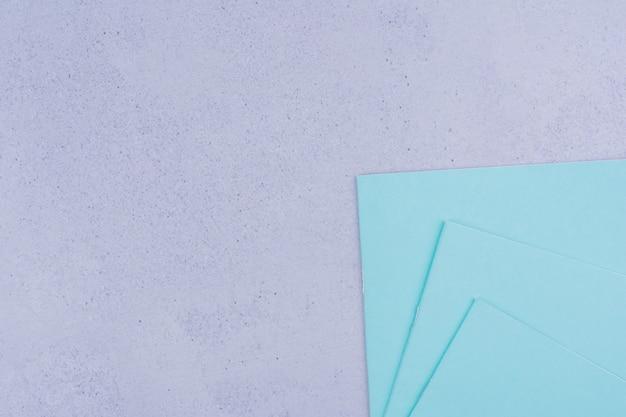 Papiery uwaga niebieski na białym tle na szarej powierzchni