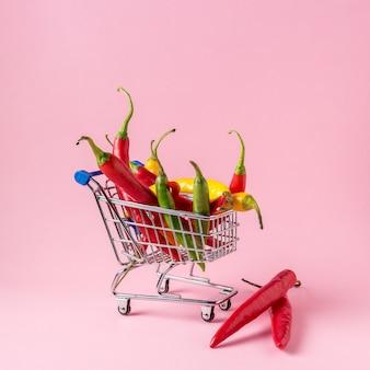 Papryczka chili w koszyku na różowej powierzchni.